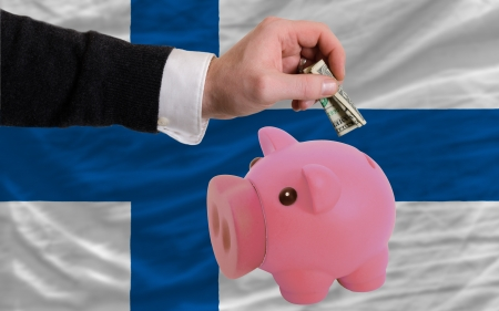 foreign national: Man putting euro into piggy rich bank and national flag of finland in foreign currency because of insecurity and inflation