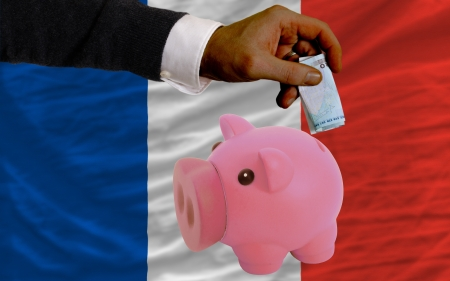 Man putting euro into piggy rich bank and national flag of france in foreign currency because of insecurity and inflation photo