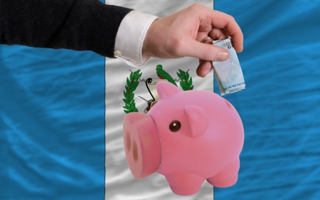 foreign national: Man putting euro into piggy rich bank and national flag of guatemala in foreign currency because of insecurity and inflation