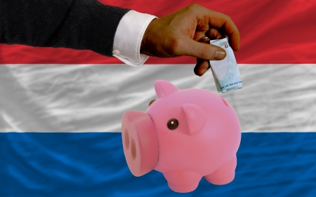 foreign national: Man putting euro into piggy rich bank and national flag of netherlands in foreign currency because of insecurity and inflation Stock Photo
