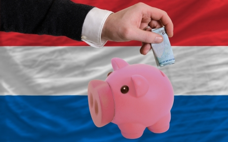 Man putting euro into piggy rich bank and national flag of netherlands in foreign currency because of insecurity and inflation Stock Photo - 18039177