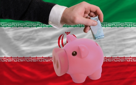 foreign national: Man putting euro into piggy rich bank and national flag of iran in foreign currency because of insecurity and inflation Stock Photo