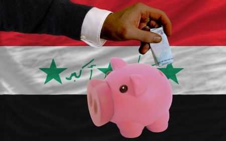 iraq money: Man putting euro into piggy rich bank and national flag of iraq in foreign currency because of insecurity and inflation