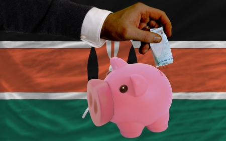 foreign national: Man putting euro into piggy rich bank and national flag of kenya in foreign currency because of insecurity and inflation