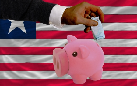 foreign national: Man putting euro into piggy rich bank and national flag of liberia in foreign currency because of insecurity and inflation Stock Photo