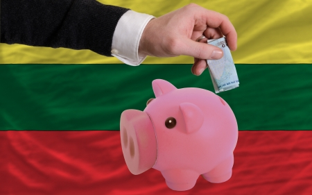 foreign national: Man putting euro into piggy rich bank and national flag of lithuania in foreign currency because of insecurity and inflation