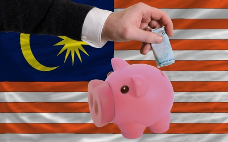 foreign national: Man putting euro into piggy rich bank and national flag of malaysia in foreign currency because of insecurity and inflation Stock Photo