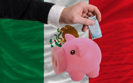 foreign national: Man putting euro into piggy rich bank and national flag of mexico in foreign currency because of insecurity and inflation