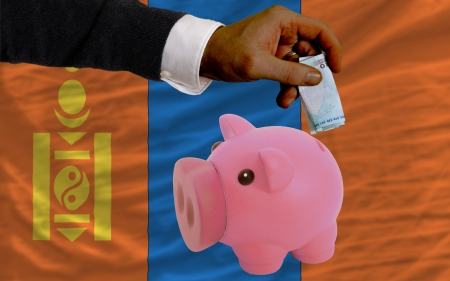 foreign national: Man putting euro into piggy rich bank and national flag of mongolia in foreign currency because of insecurity and inflation