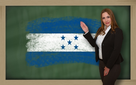 Successful, beautiful and confident woman showing flag of honduras on blackboard for marketing research, presentation and tourist advertising photo