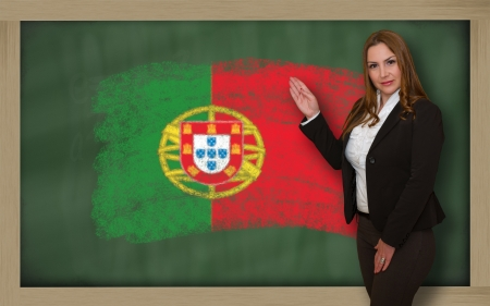 Successful, beautiful and confident woman showing flag of portugal on blackboard for marketing research, presentation and tourist advertising photo