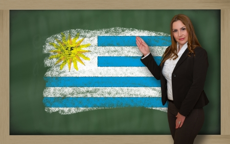 Successful, beautiful and confident woman showing flag of uruguay on blackboard for marketing research, presentation and tourist advertising photo