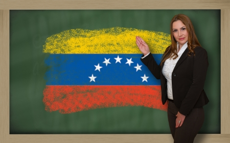 student travel: Successful, beautiful and confident woman showing flag of venezuela on blackboard for marketing research, presentation and tourist advertising