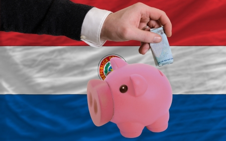 foreign national: Man putting euro into piggy rich bank and national flag of paraguay in foreign currency because of insecurity and inflation