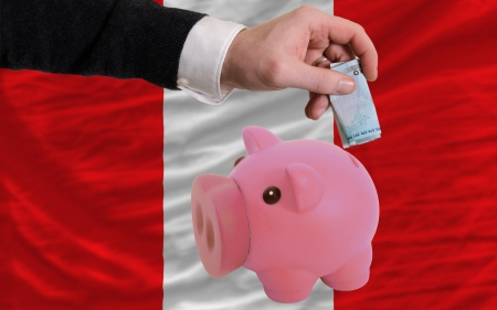 Man putting euro into piggy rich bank and national flag of peru in foreign currency because of insecurity and inflation photo