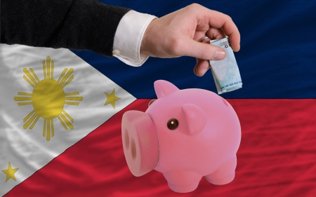 foreign national: Man putting euro into piggy rich bank and national flag of philippines in foreign currency because of insecurity and inflation