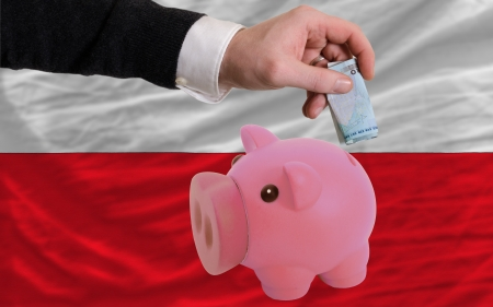 foreign national: Man putting euro into piggy rich bank and national flag of poland in foreign currency because of insecurity and inflation