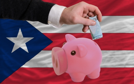 puertorico: Man putting euro into piggy rich bank and national flag of puertorico in foreign currency because of insecurity and inflation
