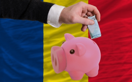 foreign national: Man putting euro into piggy rich bank and national flag of romania in foreign currency because of insecurity and inflation