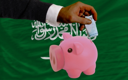 Man putting euro into piggy rich bank and national flag of  saudi arabia in foreign currency because of insecurity and inflation photo