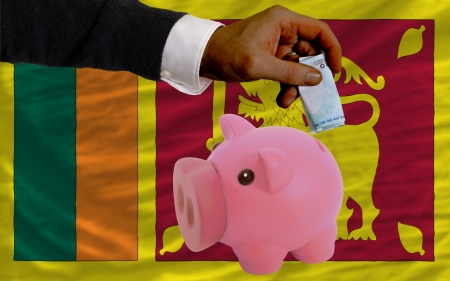 foreign national: Man putting euro into piggy rich bank and national flag of srilanka in foreign currency because of insecurity and inflation