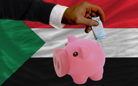 foreign national: Man putting euro into piggy rich bank and national flag of sudan in foreign currency because of insecurity and inflation Stock Photo