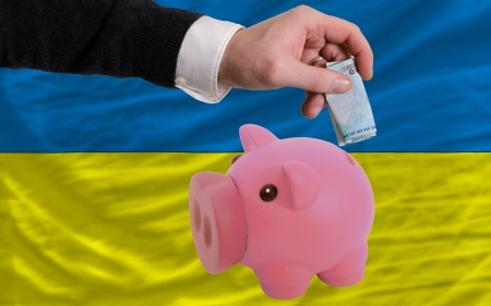 foreign national: Man putting euro into piggy rich bank and national flag of ukraine in foreign currency because of insecurity and inflation