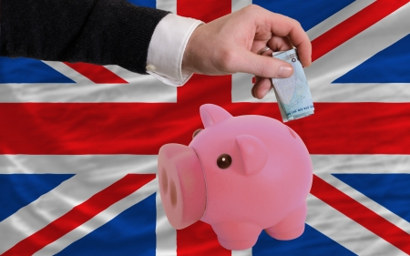 foreign national: Man putting euro into piggy rich bank and national flag of uk in foreign currency because of insecurity and inflation Stock Photo