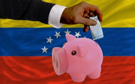 foreign national: Man putting euro into piggy rich bank and national flag of venezuela in foreign currency because of insecurity and inflation