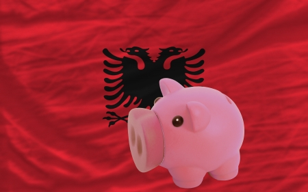 piktogramm: Piggy rich bank in front of national flag of albania symbolizing saving and accumulating funds as good financial habit