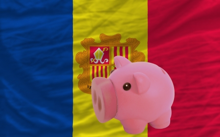 accumulating: Piggy rich bank in front of national flag of andorra symbolizing saving and accumulating funds as good financial habit