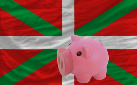 accumulating: Piggy rich bank in front of national flag of  basque symbolizing saving and accumulating funds as good financial habit