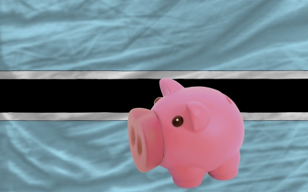 piktogramm: Piggy rich bank in front of national flag of botswana symbolizing saving and accumulating funds as good financial habit