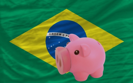 accumulating: Piggy rich bank in front of national flag of brazil symbolizing saving and accumulating funds as good financial habit