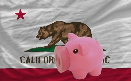 accumulating: Piggy rich bank in front of flag of us state of california symbolizing saving and accumulating funds as good financial habit Stock Photo
