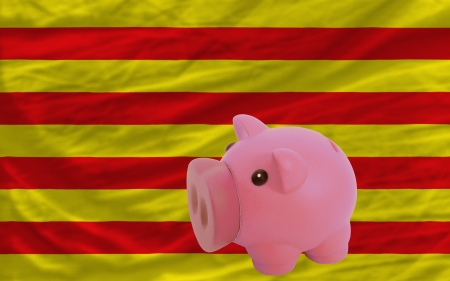 accumulating: Piggy rich bank in front of national flag of  catalonia symbolizing saving and accumulating funds as good financial habit