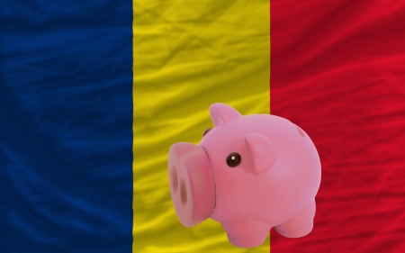 chadian: Piggy rich bank in front of national flag of  chad symbolizing saving and accumulating funds as good financial habit