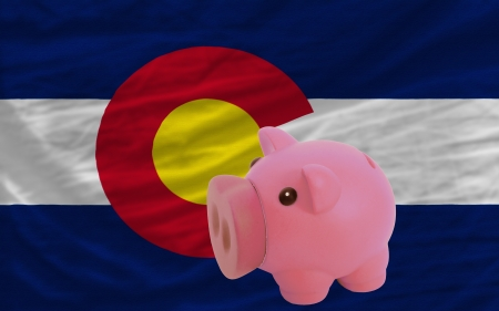 accumulating: Piggy rich bank in front of flag of us state of colorado symbolizing saving and accumulating funds as good financial habit Stock Photo