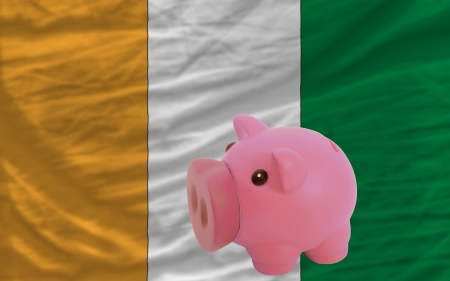 accumulating: Piggy rich bank in front of national flag of cote ivore symbolizing saving and accumulating funds as good financial habit Stock Photo