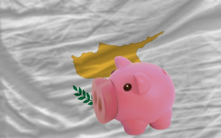 accumulating: Piggy rich bank in front of national flag of cyprus symbolizing saving and accumulating funds as good financial habit