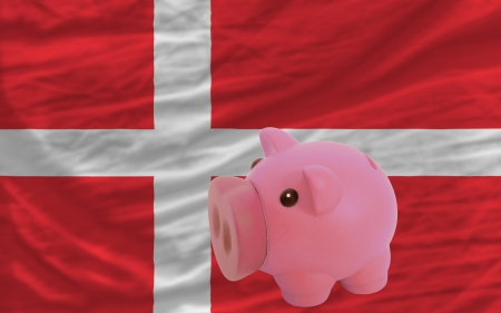 accumulating: Piggy rich bank in front of national flag of denmark symbolizing saving and accumulating funds as good financial habit Stock Photo