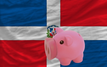 accumulating: Piggy rich bank in front of national flag of dominican symbolizing saving and accumulating funds as good financial habit