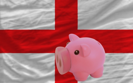 accumulating: Piggy rich bank in front of national flag of england symbolizing saving and accumulating funds as good financial habit