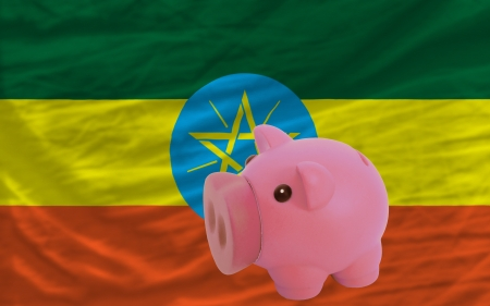 accumulating: Piggy rich bank in front of national flag of ethiopia symbolizing saving and accumulating funds as good financial habit