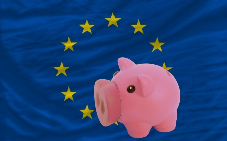 Piggy rich bank in front of national flag of europe symbolizing saving and accumulating funds as good financial habit photo