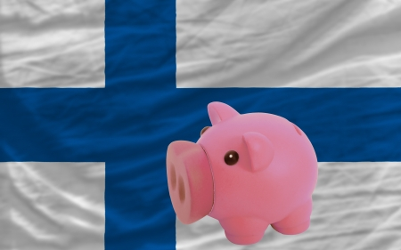 accumulating: Piggy rich bank in front of national flag of finland symbolizing saving and accumulating funds as good financial habit