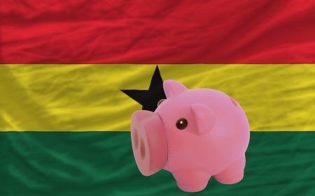accumulating: Piggy rich bank in front of national flag of ghana symbolizing saving and accumulating funds as good financial habit