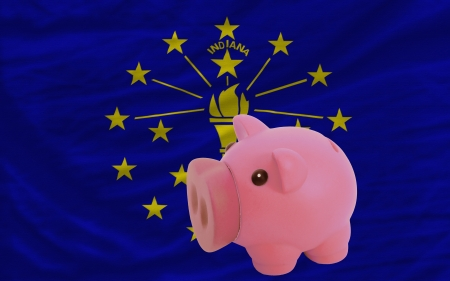 accumulating: Piggy rich bank in front of flag of us state of indiana symbolizing saving and accumulating funds as good financial habit Stock Photo