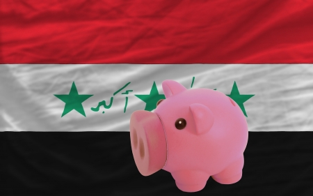 accumulating: Piggy rich bank in front of national flag of iraq symbolizing saving and accumulating funds as good financial habit