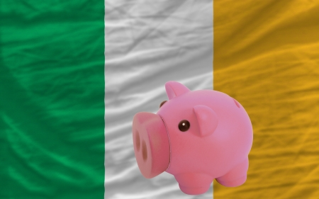 accumulating: Piggy rich bank in front of national flag of ireland symbolizing saving and accumulating funds as good financial habit